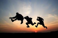 Silhuetas de um salto de três homens Foto de Stock