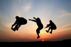 Silhuetas de um salto de três homens Imagens de Stock Royalty Free