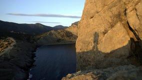 Silhuetas do aperto dos pares Silhueta em uma rocha no mar durante o por do sol Aprecie seus férias e curso junto filme