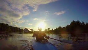 Silhuetas do esporte de barco dos povos no por do sol, viagem, slowmotion video estoque