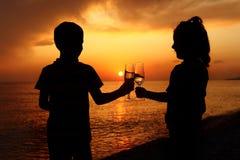 Silhuetas do menino e da menina com vidros no por do sol Imagens de Stock