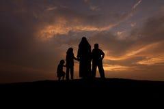 Silhuetas do mulheres muçulmanas com ela criança Fotos de Stock Royalty Free