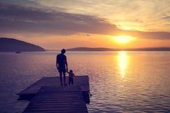 Silhuetas do pai com seu filho pelo mar fotos de stock