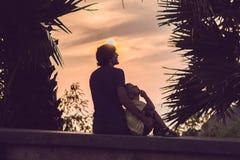 Silhuetas do pai e do filho, que encontram o por do sol nos trópicos contra o contexto das palmeiras imagem de stock