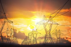 Silhuetas do polo da transmissão da eletricidade no por do sol fotografia de stock royalty free