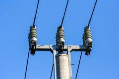 Silhuetas do polo e de linhas elétricas de alta tensão foto de stock