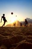 Silhuetas do por do sol que jogam o futebol Brasil da praia de Altinho Futebol Imagem de Stock
