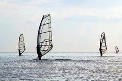 Silhuetas do quatro windsurfers imagens de stock