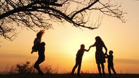 Silhuetas do tempo da despesa da família junto no prado próximo durante o por do sol vídeos de arquivo