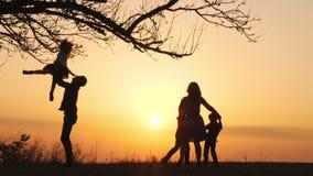 Silhuetas do tempo da despesa da família junto no prado próximo durante o por do sol filme