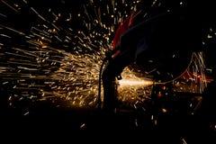 Silhuetas do trabalhador e faíscas da fogueira ao moer o ferro Foto de Stock
