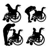 Silhuetas do vetor do cão em uma cadeira de rodas Foto de Stock Royalty Free