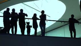 Silhuetas dos adultos e das crianças que estão perto do corrimão vítreo na construção moderna Fotografia de Stock