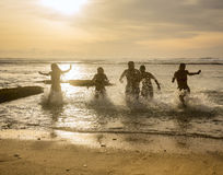 Silhuetas dos amigos que correm fora do oceano Foto de Stock Royalty Free
