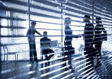 Silhuetas dos executivos através das cortinas Imagens de Stock