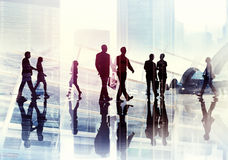 Silhuetas dos executivos que andam dentro do escritório Fotografia de Stock Royalty Free
