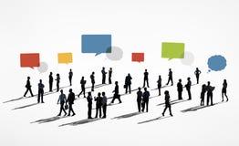 Silhuetas dos executivos que trabalham e das bolhas do discurso acima Imagens de Stock Royalty Free