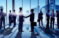 Silhuetas dos homens de negócios que têm um aperto de mão Foto de Stock Royalty Free