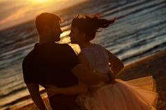 Silhuetas dos homens e das mulheres na saia curto luxúria, beijando o AG Fotos de Stock Royalty Free