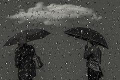 Silhuetas dos homens e das mulheres sob guarda-chuvas Foto de Stock Royalty Free