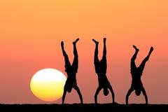 Silhuetas dos indivíduos no fundo do por do sol Fotos de Stock Royalty Free
