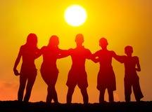 Silhuetas dos meninos e das meninas que abraçam na praia Imagens de Stock