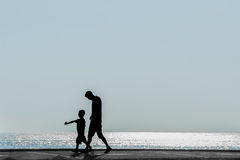 Silhuetas dos pais com o bebê no fundo do mar Fotografia de Stock Royalty Free