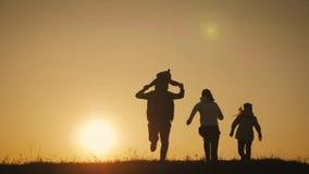 Silhuetas dos pais felizes que t?m o bom tempo com suas crian?as pequenas no exterior no por do sol video estoque