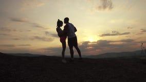 Silhuetas dos pares aptos da raça misturada que fazem o exercício exterior no fundo das montanhas rochosas no por do sol Aptidão  filme