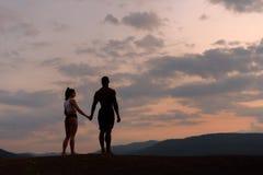 Silhuetas dos pares ginásticos atléticos que olham o nascer do sol junto O corpo de ser humano perfeito Imagens de Stock