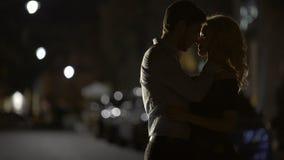 Silhuetas dos pares loving que abraçam-se na rua, relacionamento vídeos de arquivo