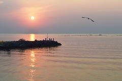 Silhuetas dos pescadores no quebra-mar no nascer do sol Fotografia de Stock Royalty Free
