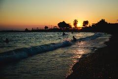 Silhuetas dos povos felizes que nadam e que jogam no mar no por do sol, conceito sobre ter o divertimento na praia imagens de stock