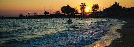 Silhuetas dos povos felizes que nadam e que jogam no mar no por do sol, conceito sobre ter o divertimento na praia fotos de stock