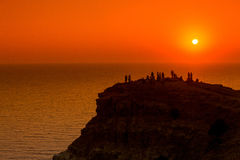 Silhuetas dos povos no por do sol no penhasco sobre o mar Foto de Stock Royalty Free