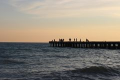 Silhuetas dos povos, provavelmente pescadores no cais no mar imagens de stock royalty free