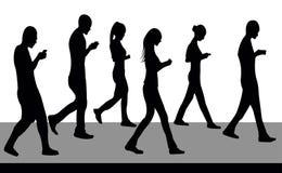 Silhuetas dos povos que andam e com telefones Imagem de Stock