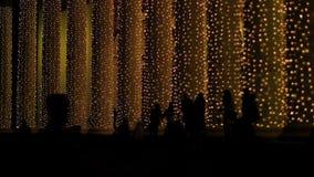 Silhuetas dos povos que andam perto das colunas gigantescas brilhantemente iluminadas, feriados filme