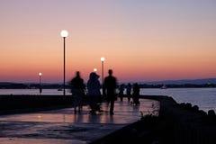 Silhuetas dos povos que andam perto do mar no por do sol Foto de Stock
