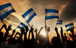 Silhuetas dos povos que guardam a bandeira das Honduras Imagem de Stock Royalty Free