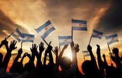 Silhuetas dos povos que guardam a bandeira de Argentina Imagens de Stock