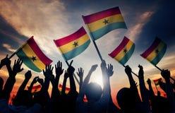 Silhuetas dos povos que guardam a bandeira de Gana foto de stock