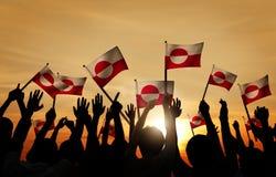 Silhuetas dos povos que guardam a bandeira de Gronelândia imagem de stock