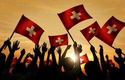 Silhuetas dos povos que guardam a bandeira de Suíça Fotos de Stock Royalty Free