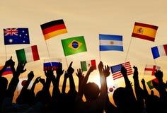 Silhuetas dos povos que guardam bandeiras dos vários países Fotografia de Stock Royalty Free