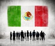 Silhuetas dos povos que olham a bandeira mexicana fotos de stock