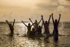 Silhuetas dos povos que saltam no oceano Fotografia de Stock