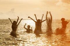 Silhuetas dos povos que saltam no oceano Fotografia de Stock Royalty Free