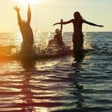 Silhuetas dos povos que saltam no oceano Imagem de Stock