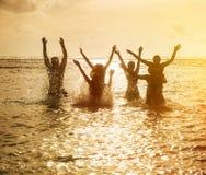 Silhuetas dos povos que saltam no oceano Fotos de Stock Royalty Free
